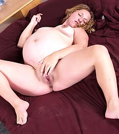 Curvy pregnant pornstar naked in bed and examining her pink pussy lips with her fingers
